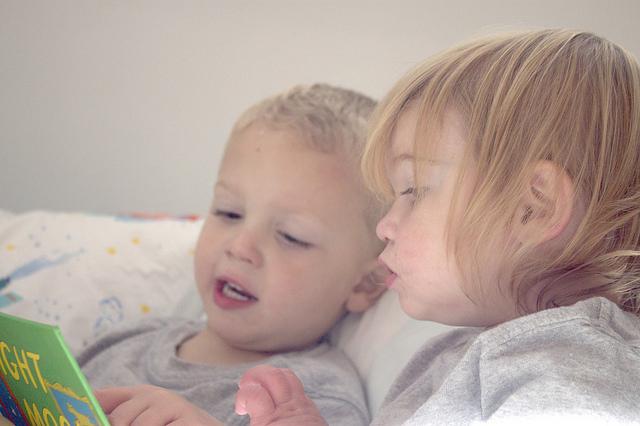 Niños en la cama leyendo
